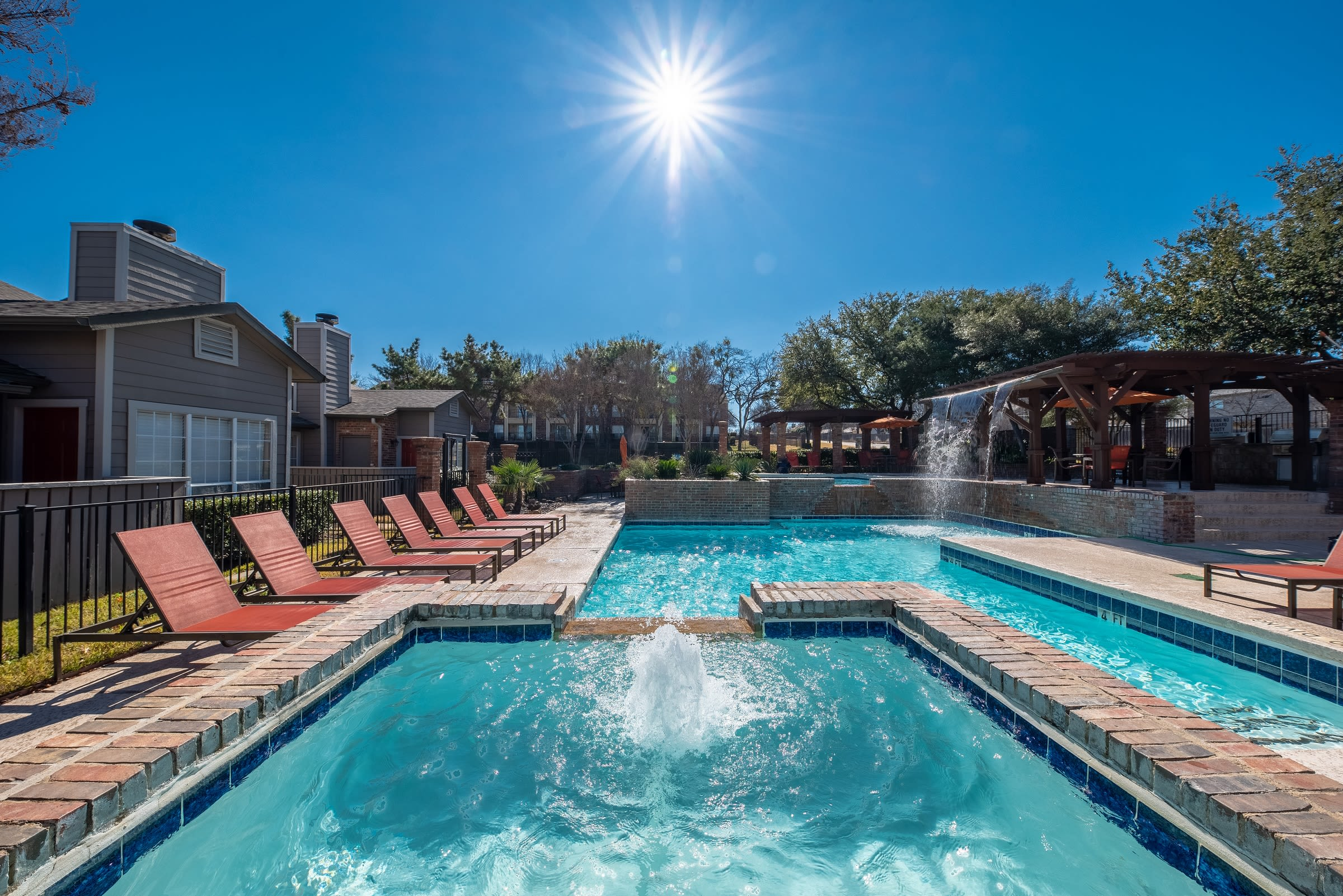 Lounge chairs poolside at Village Green of Bear Creek in Euless, Texas