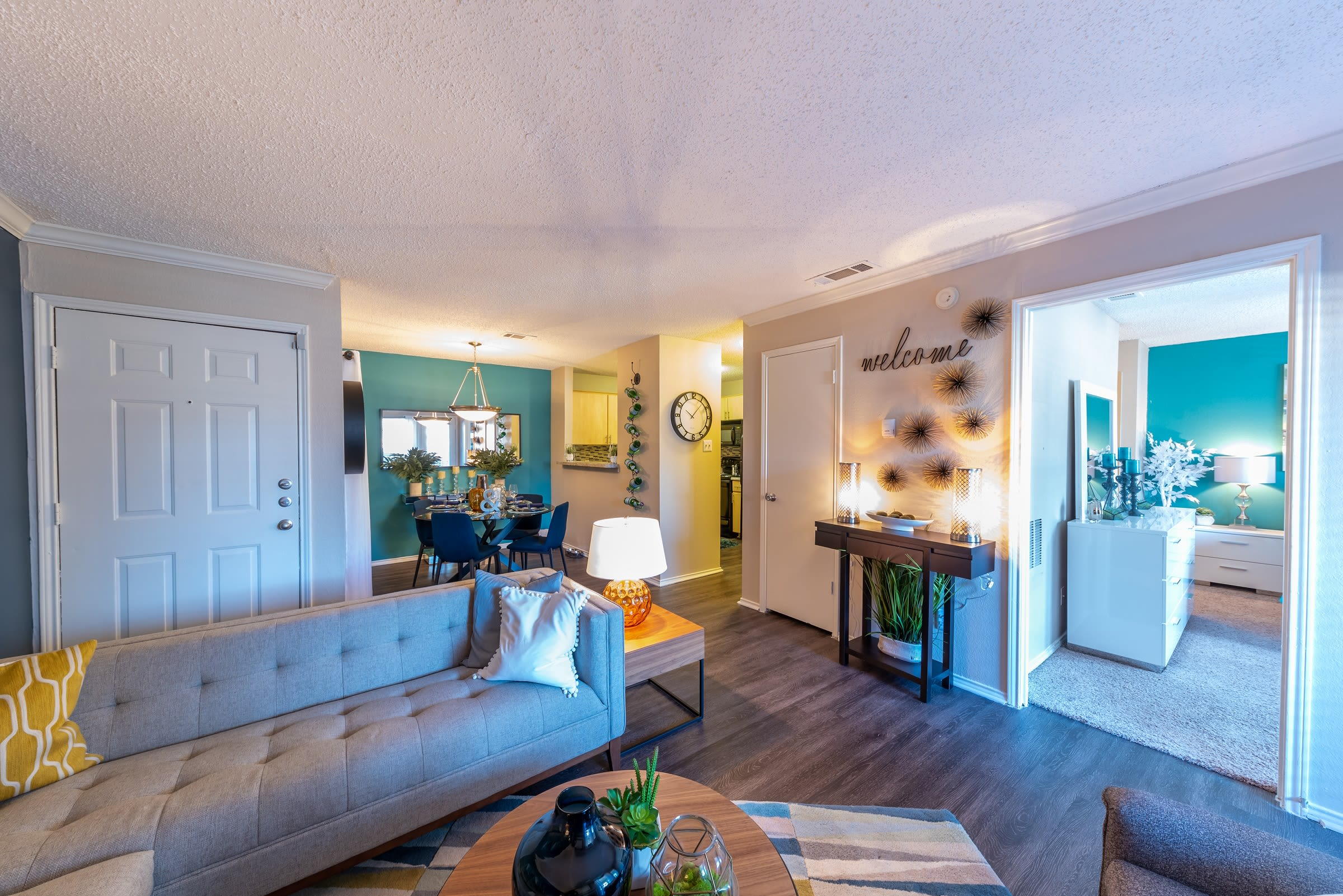 Open concept floor plan with hardwood floors and modern decor at Village Green of Bear Creek in Euless, Texas