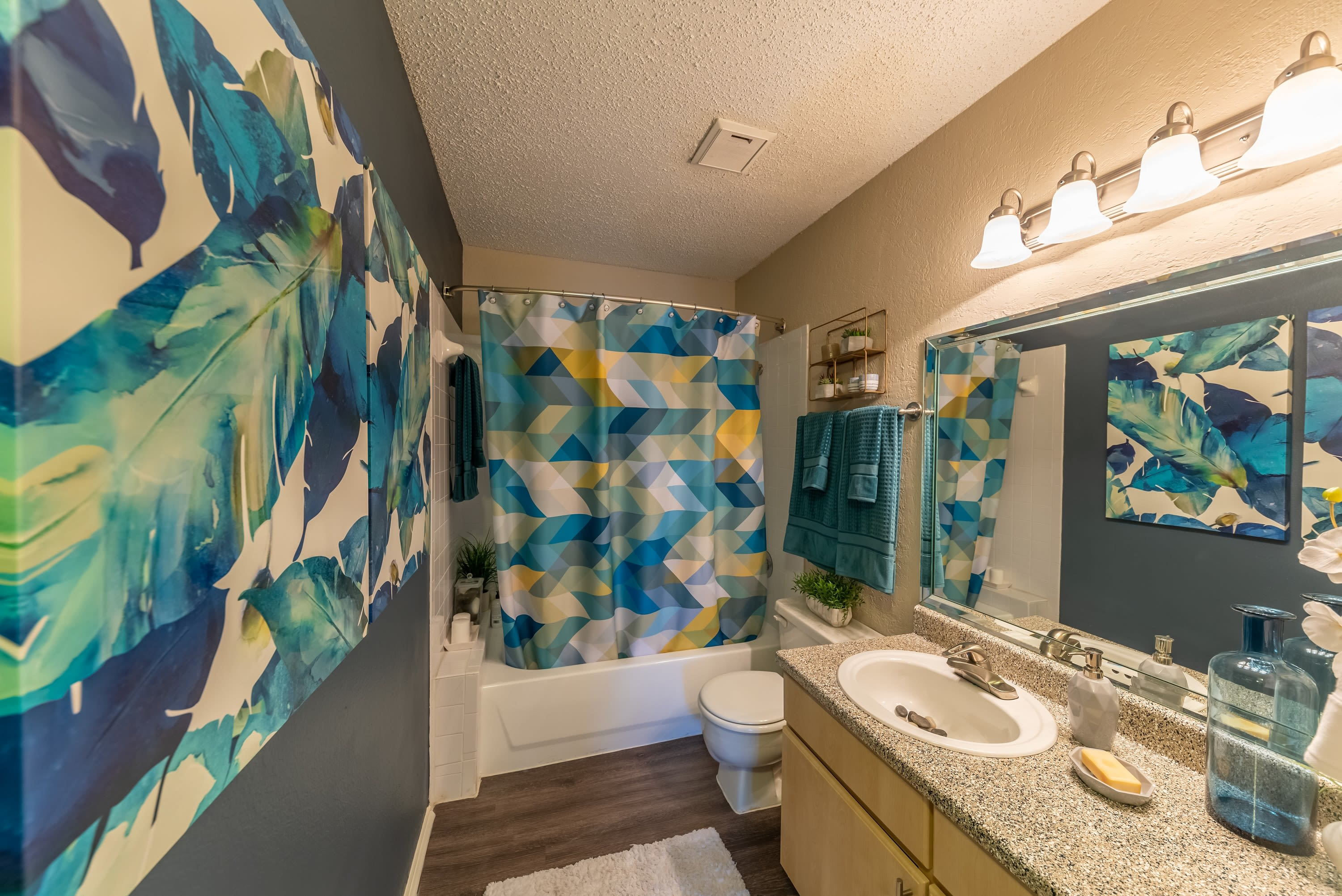 Model bathroom with large vanity mirror and oval tub at Village Green of Bear Creek in Euless, Texas