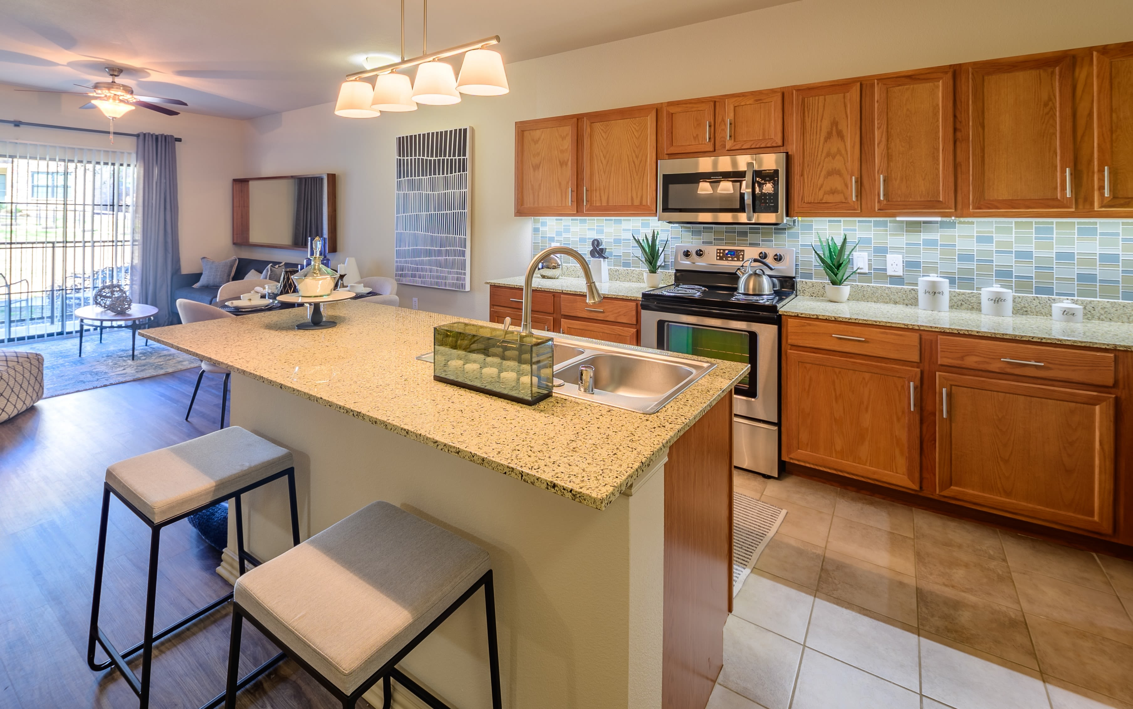 Kitchen with granite countertops and wood cabinets at Evolv in Mansfield, Texas