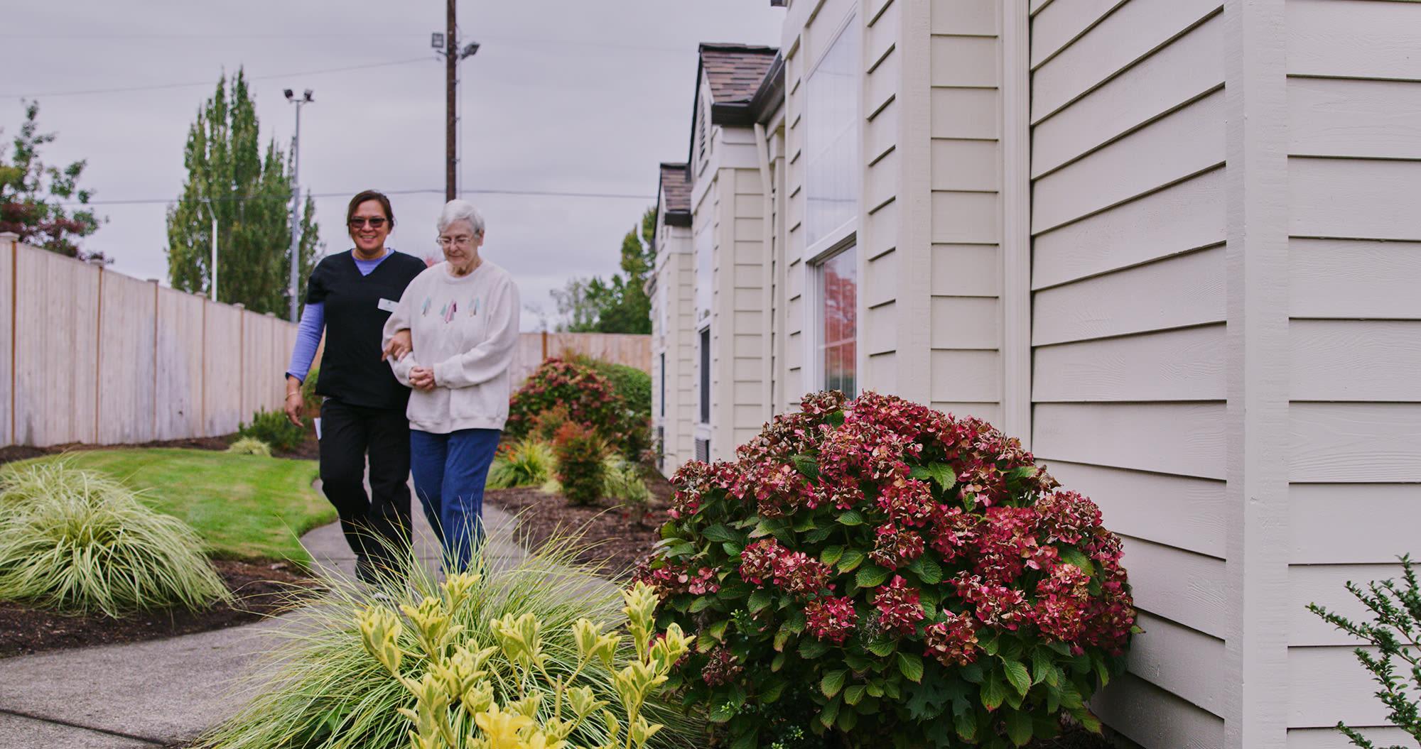 resident and a caretaker walking outside at Farmington Square Beaverton in Beaverton, Oregon
