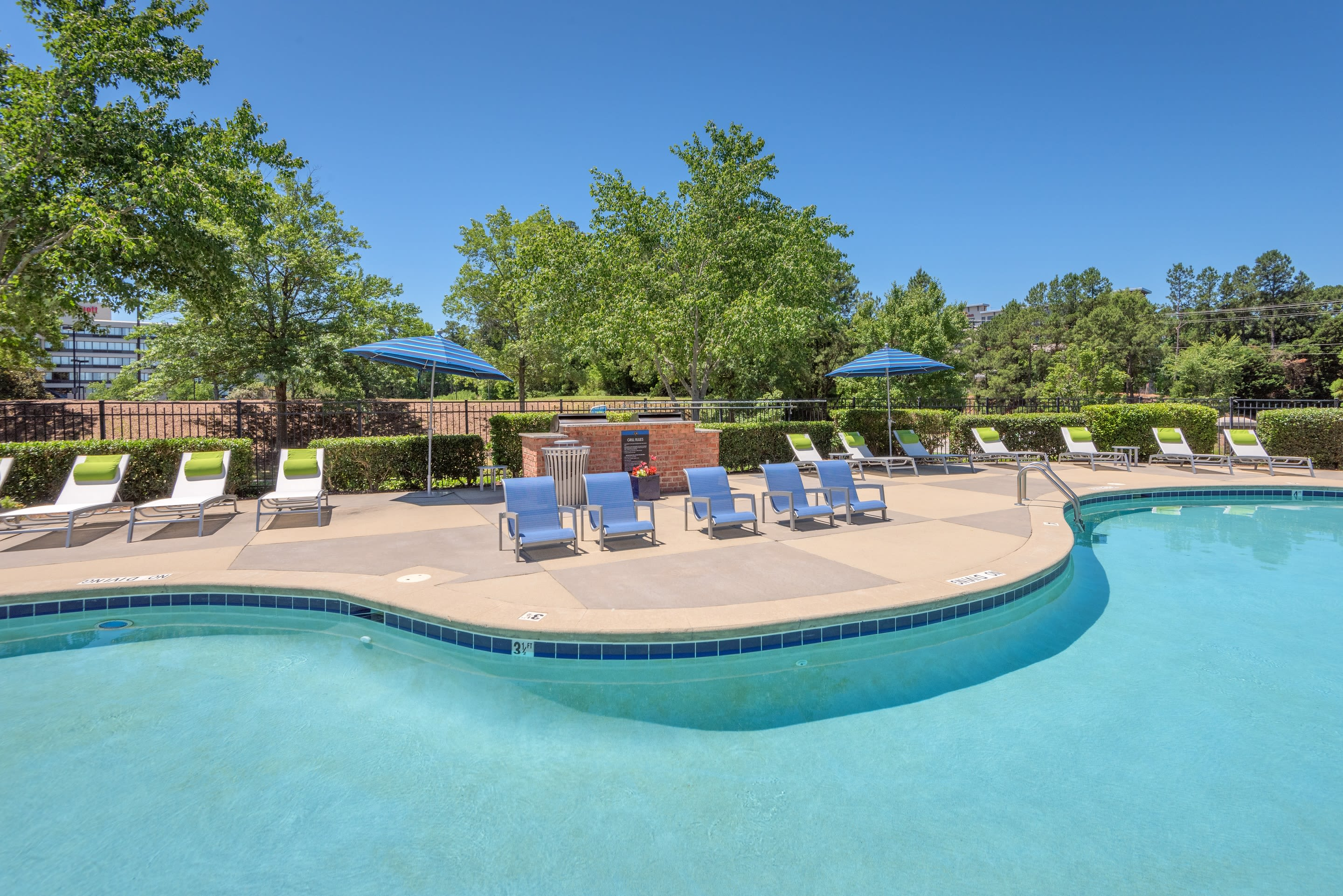 Resort-style swimming pool with plenty of chaise lounge chairs nearby at 200 East in Durham, North Carolina