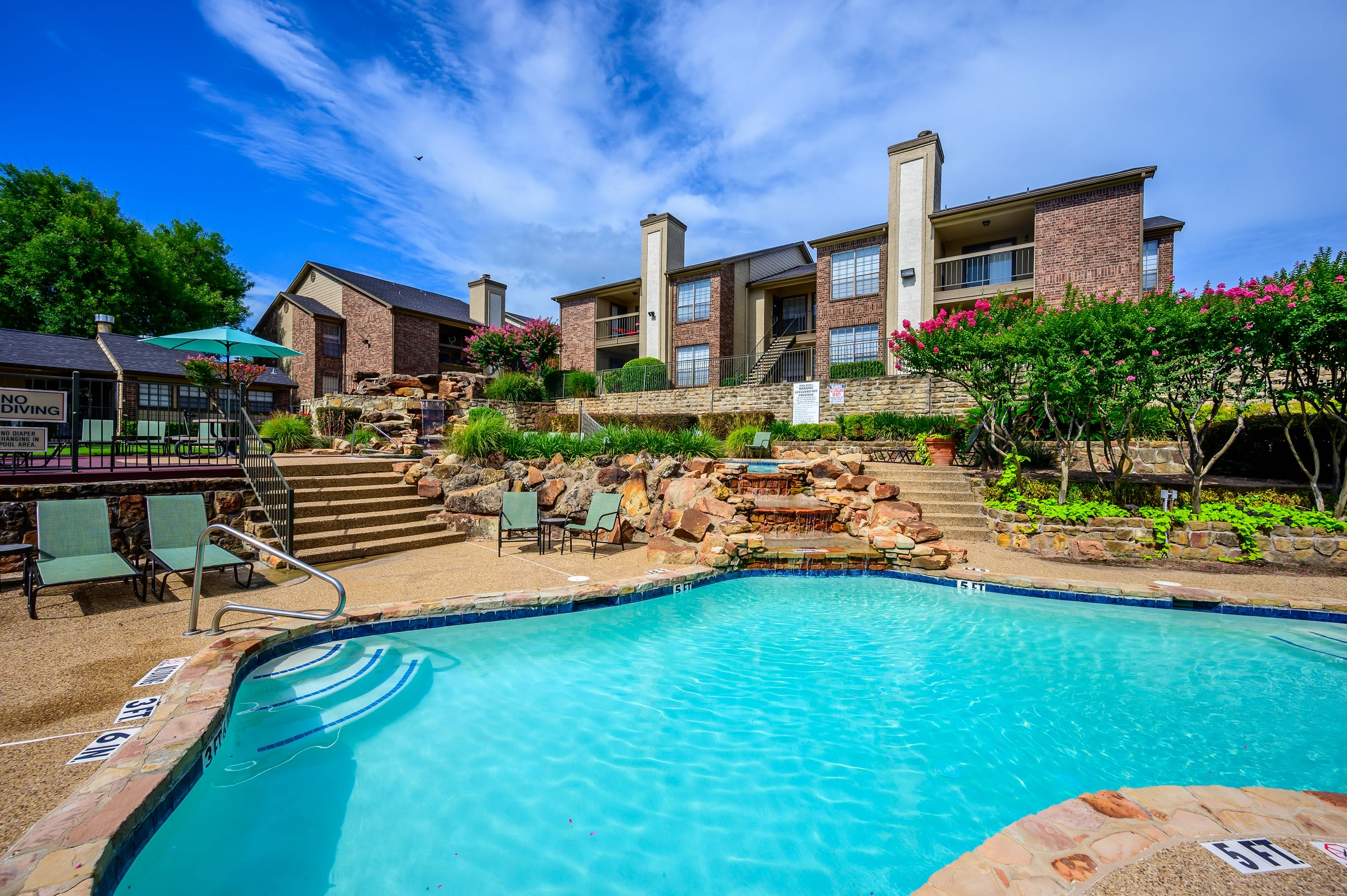 Resort-style swimming pool with a spacious sundeck and waterfall at Laurel Heights at Cityview in Fort Worth, Texas