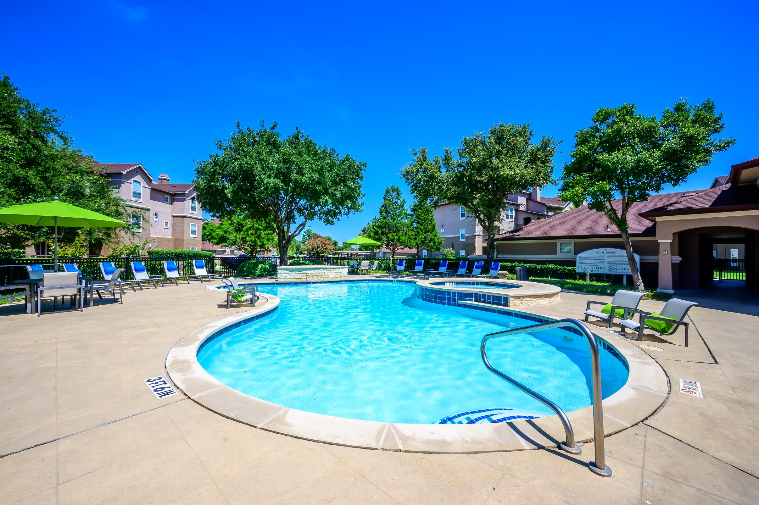 Large swimming pool with chaise lounge chairs on a beautiful sunny day at The View at Lakeside in Lewisville, Texas
