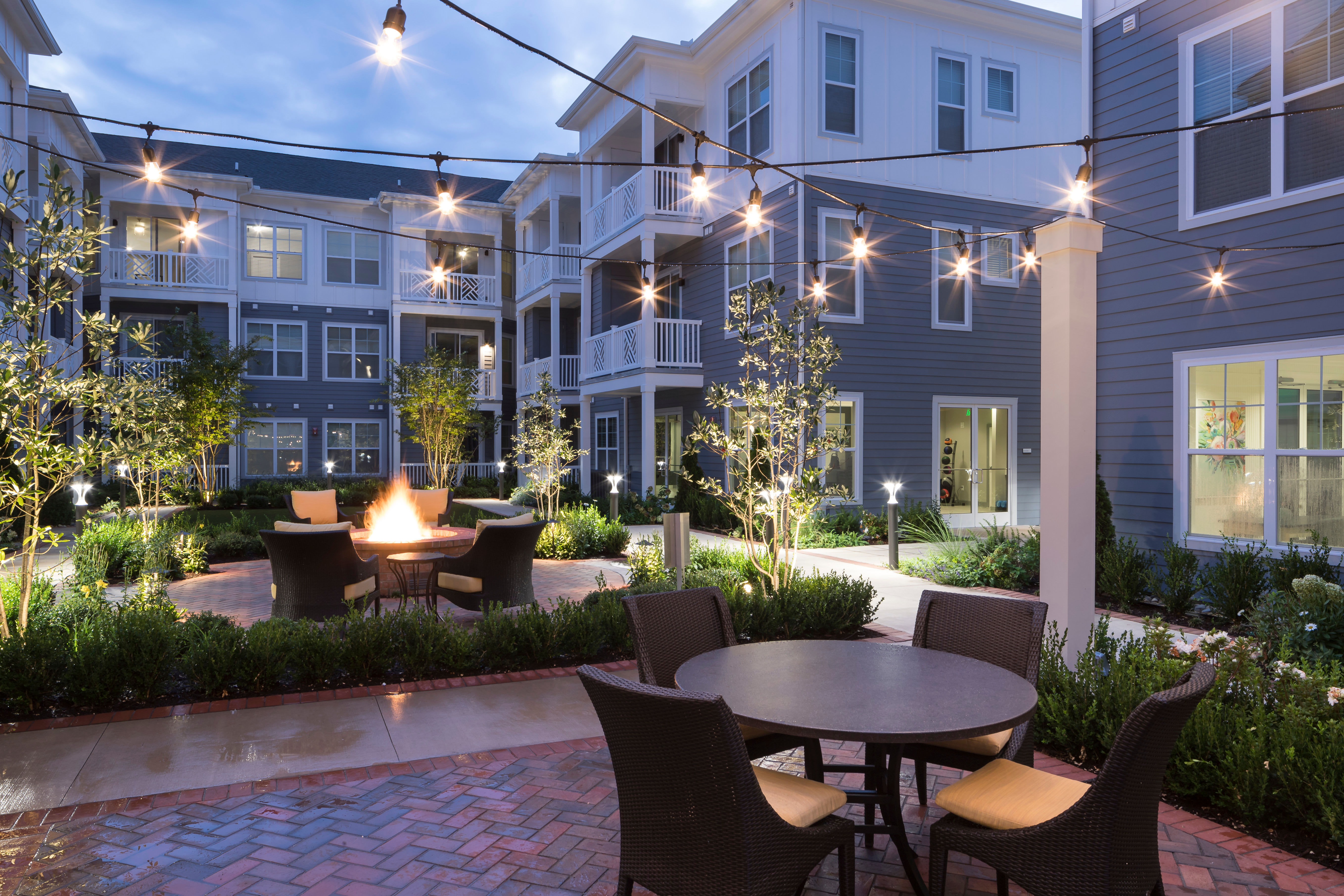 Outdoor tables and lighting - Avenida Cool Springs Active Senior Living in Franklin, TN