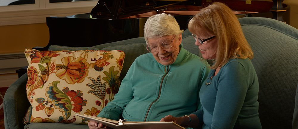Resident and a caretaker looking through a photo album at Symphony Manor in Baltimore, Maryland