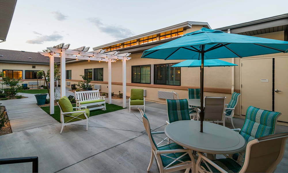 Outdoor patio with tables and umbrellas at The Wentworth at the Meadows in Saint George, Utah