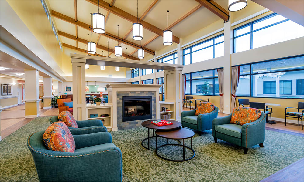 Community sitting area with lots of natural light, a fireplace and vaulted ceilings at The Wentworth at the Meadows in Saint George, Utah