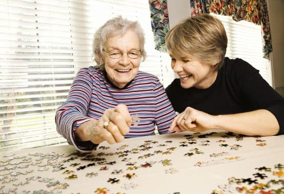 A lady puts together a puzzle with friend at Reunion Court of The Woodlands in The Woodlands, Texas