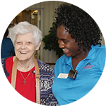 A resident and caregiver laugh together at West Fork Village in Irving, Texas