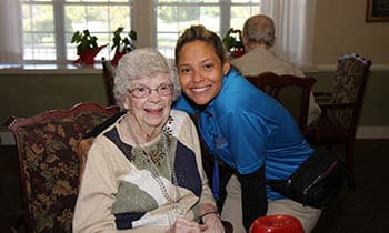 Caregiver and resident smiling for a photo at West Fork Village in Irving, Texas