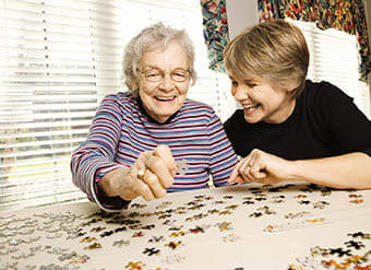 Woman doing a puzzle at West Fork Village in Irving, Texas