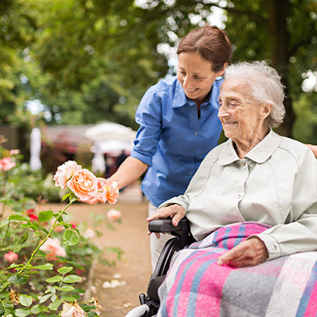 A caretaker and resident looking at flowers at The Legacy at Southpointe Drive in Greenville, South Carolina