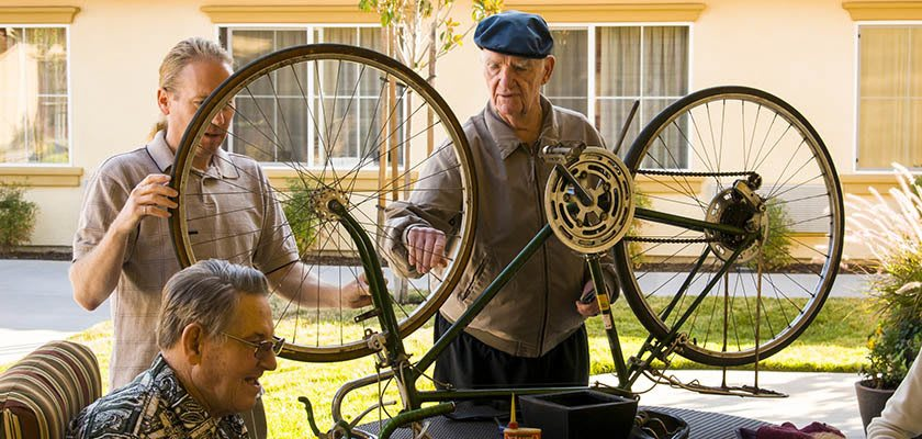 Residents fixing a bike together at Eagle Ridge Alzheimer's Special Care Center in Denton, Texas