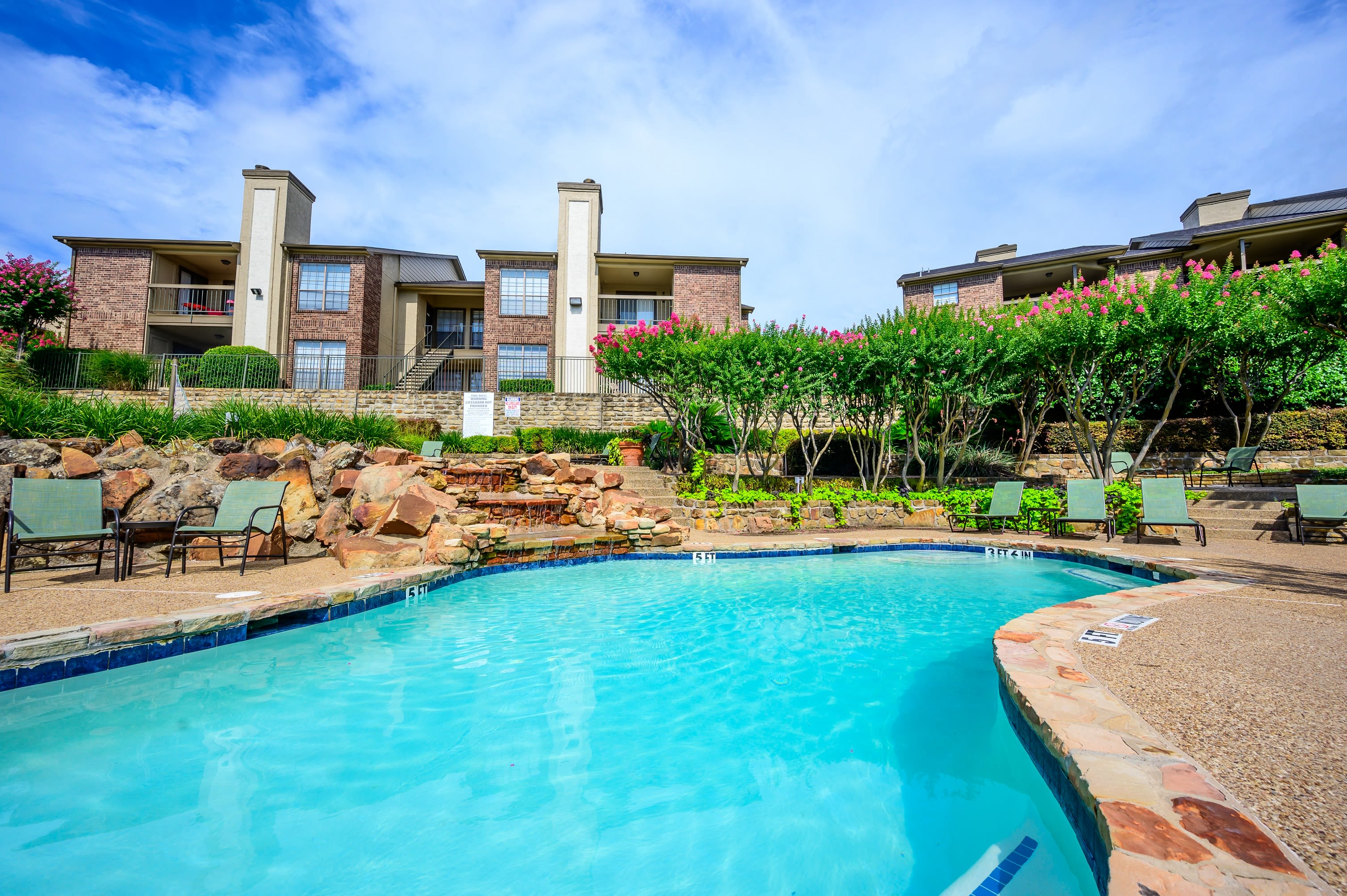 Resort-style swimming pool with waterfall at Laurel Heights at Cityview in Fort Worth, Texas