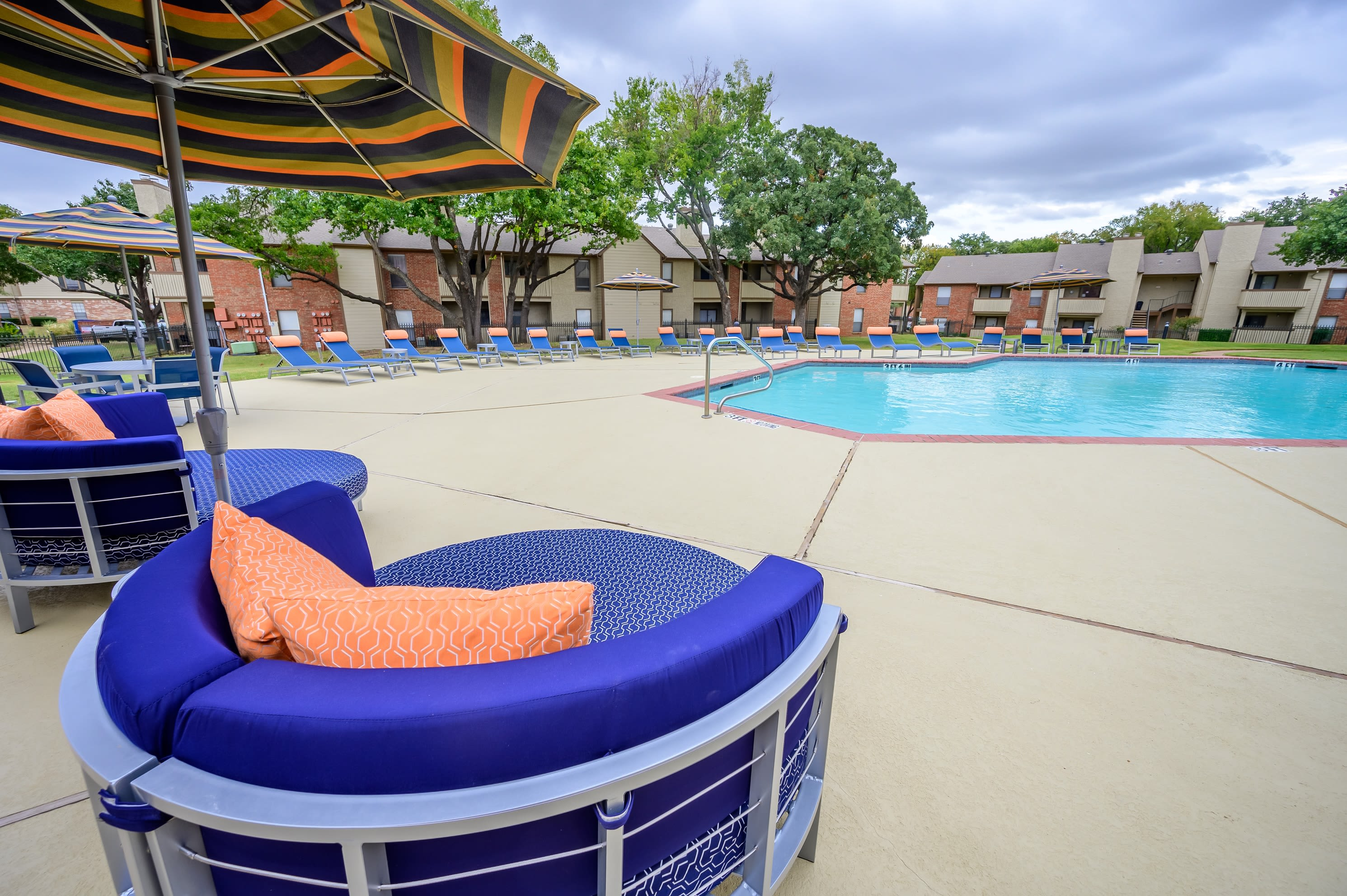 Pool with comfy chairs to sit in around it at The Logan in Bedford, Texas