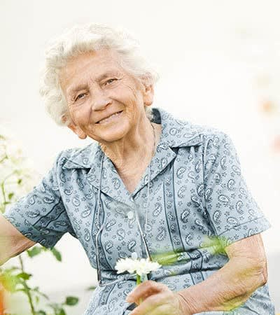Happy resident holding a flower at Creekside Alzheimer's Special Care Center in Pearland, Texas