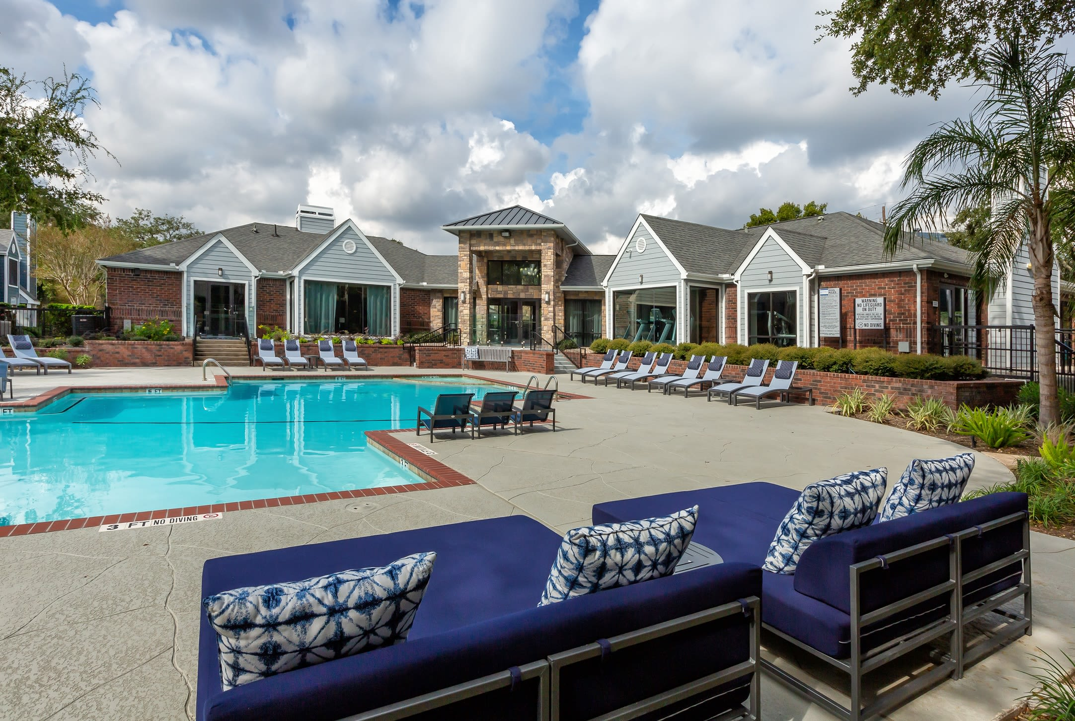 Lounge chairs poolside outside of units at Hayden at Enclave in Houston, Texas
