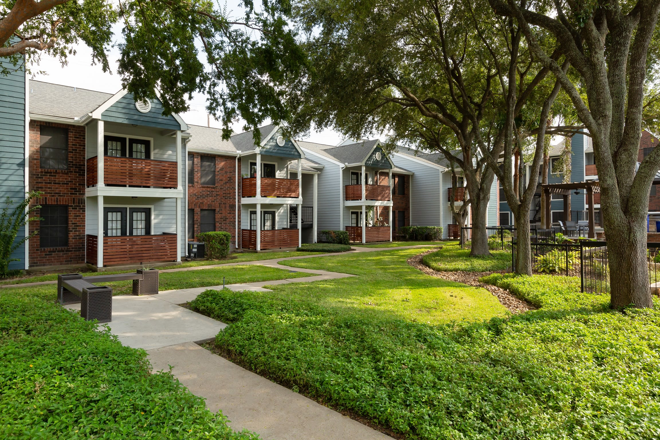 Large green courtyard with walkways at Hayden at Enclave in Houston, Texas