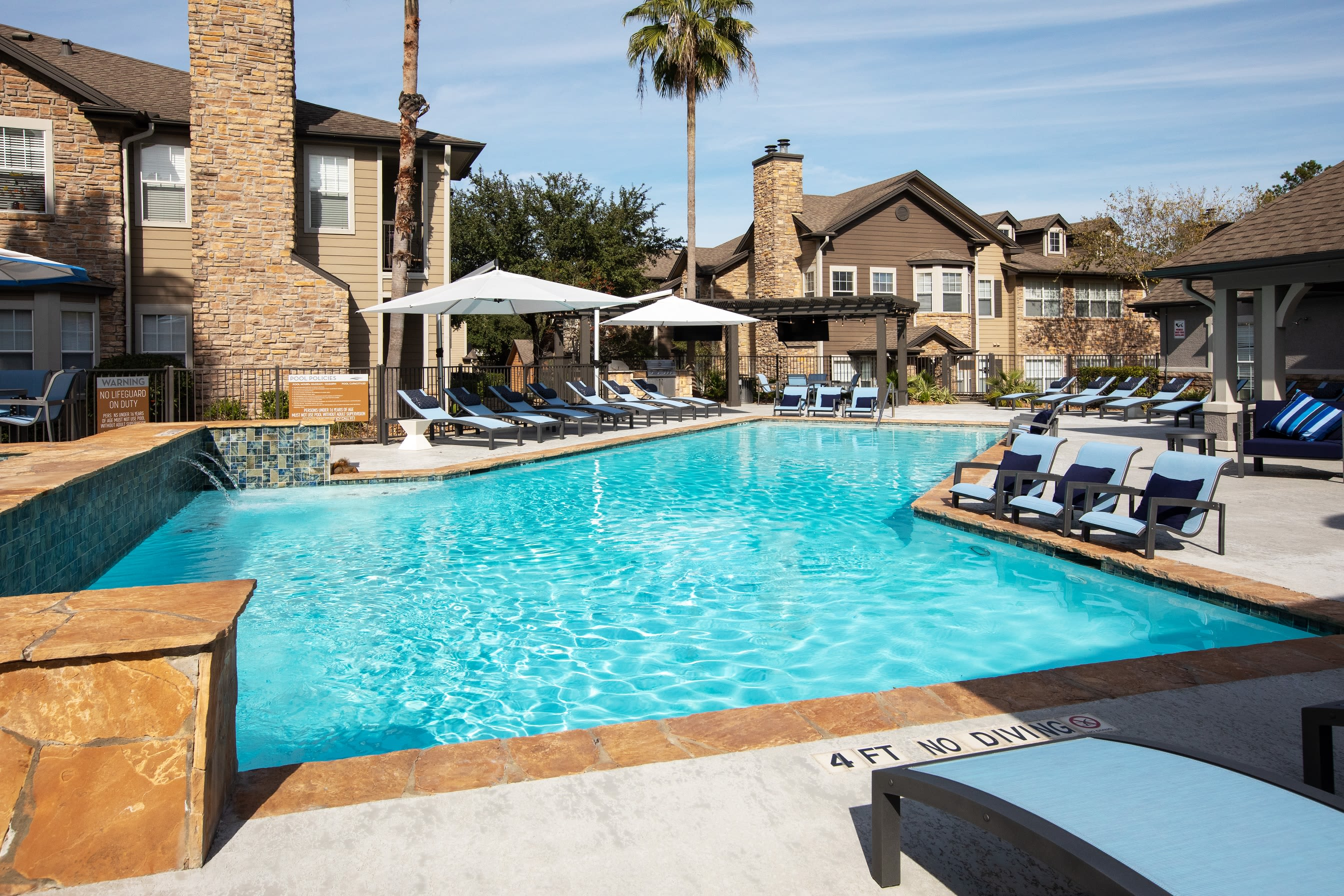 Large outdoor pool with lounge chairs and umbrellas at Artisan at Lake Wyndemere in The Woodlands, Texas