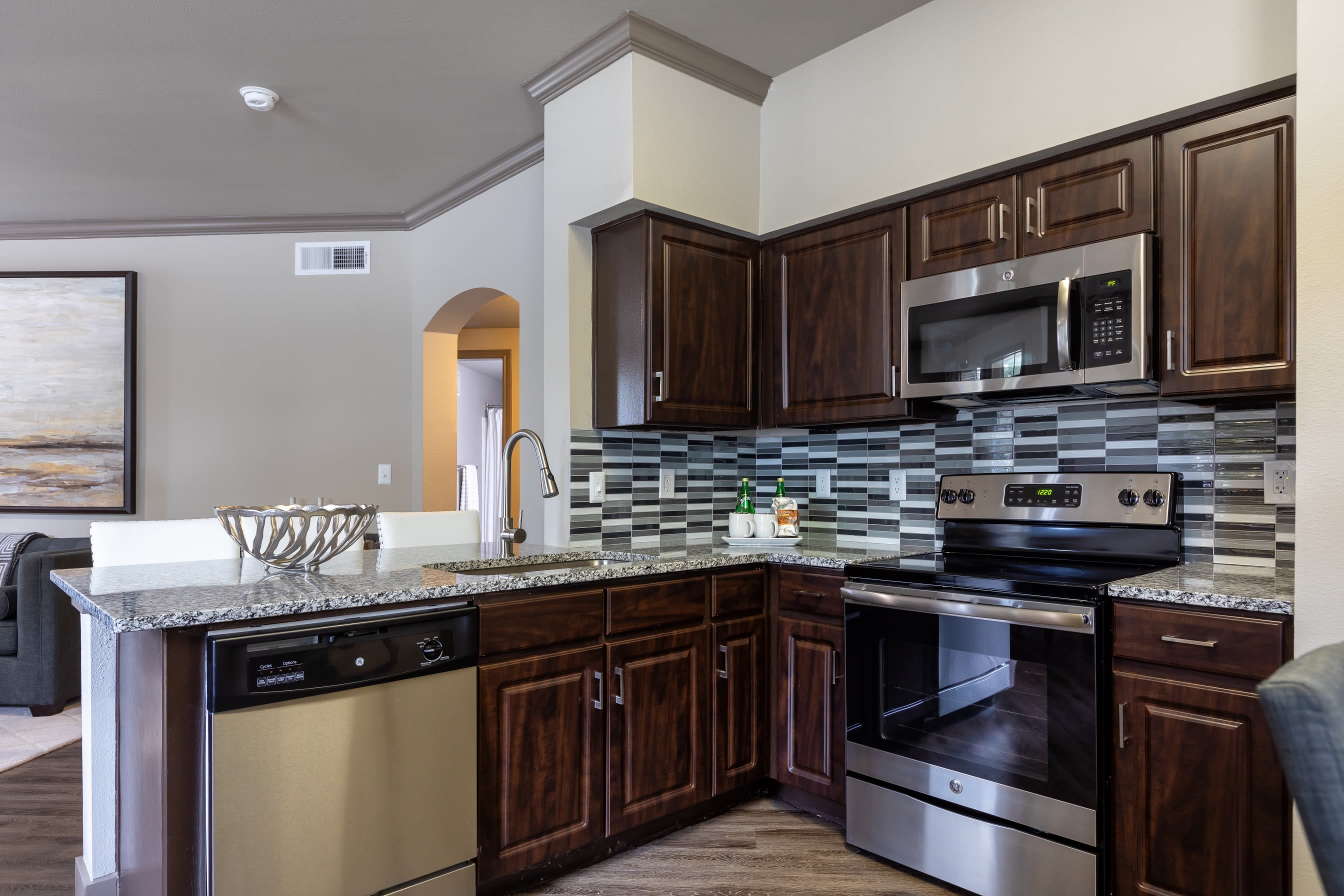 Modern kitchen with dark brown cabinetry and granite countertops at Artisan at Lake Wyndemere in The Woodlands, Texas
