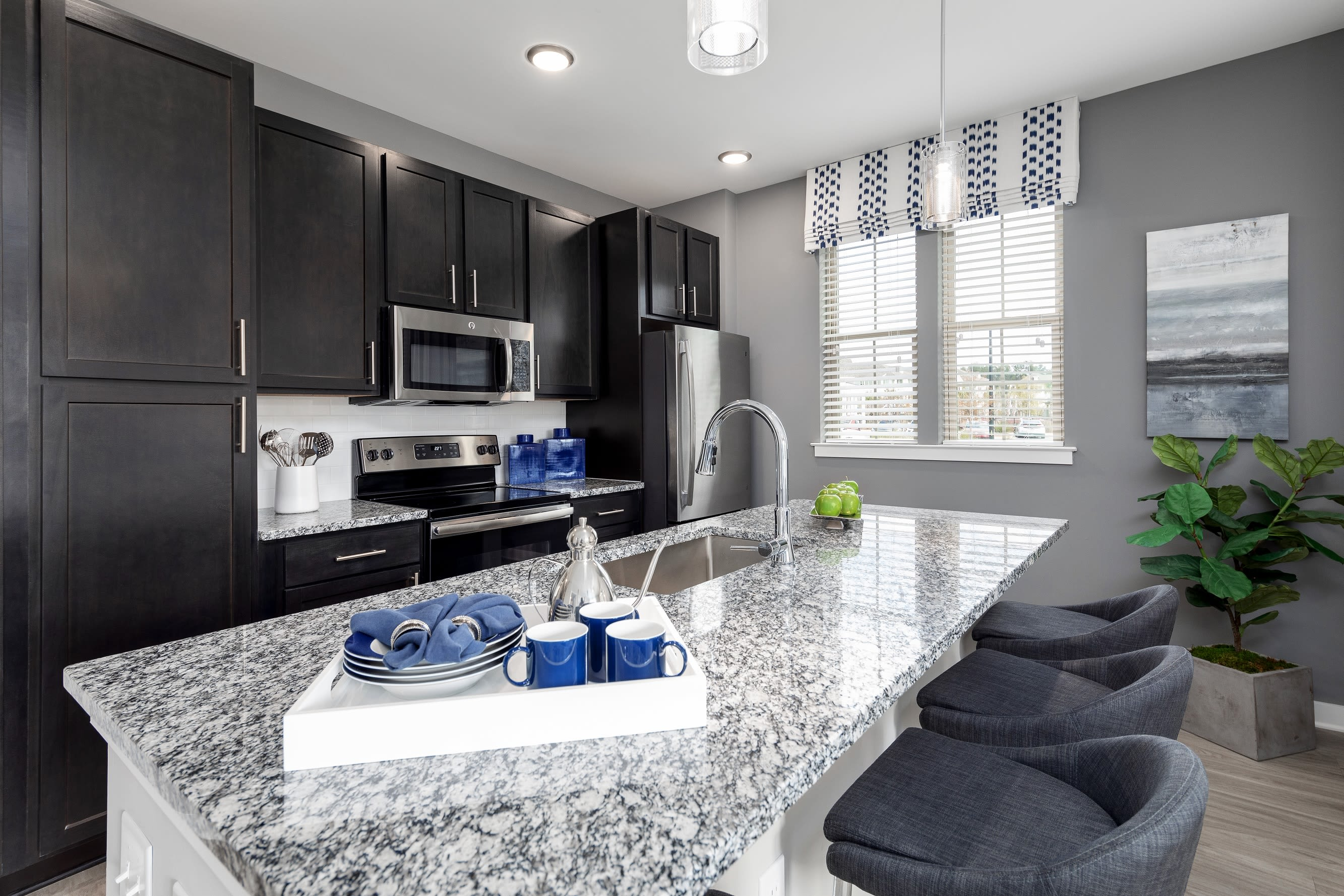 Kitchen with large granite island countertop at Elevate at Brighton Park in Summerville, South Carolina