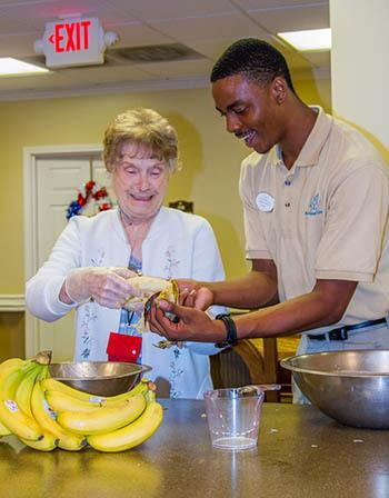 Senior woman and an employee at The Retreat at Jasper baking in Jasper, Georgia