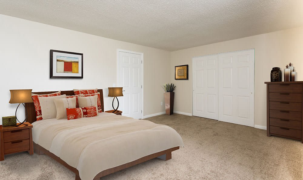 Bedroom with plush carpet at Crossroads Apartments in Spencerport, New York