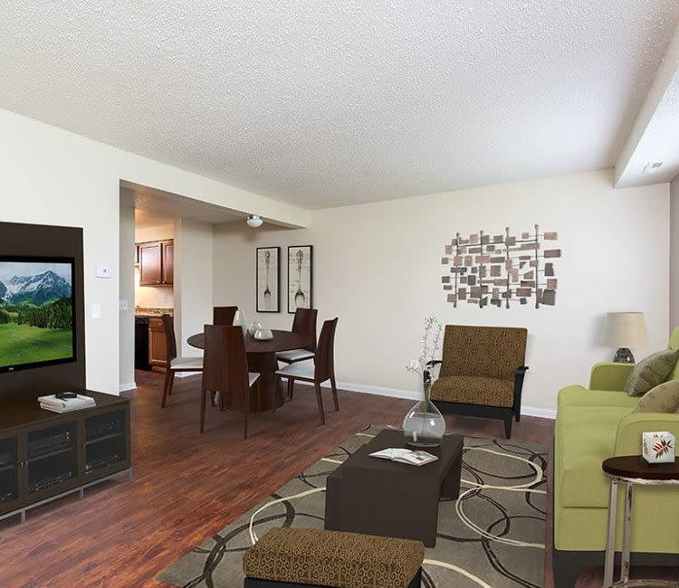 Living room with wood-style flooring at Crossroads Apartments in Spencerport, New York