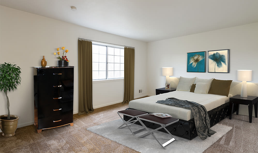 Bright, cozy bedroom at Elmwood Terrace Apartments & Townhomes in Rochester, New York