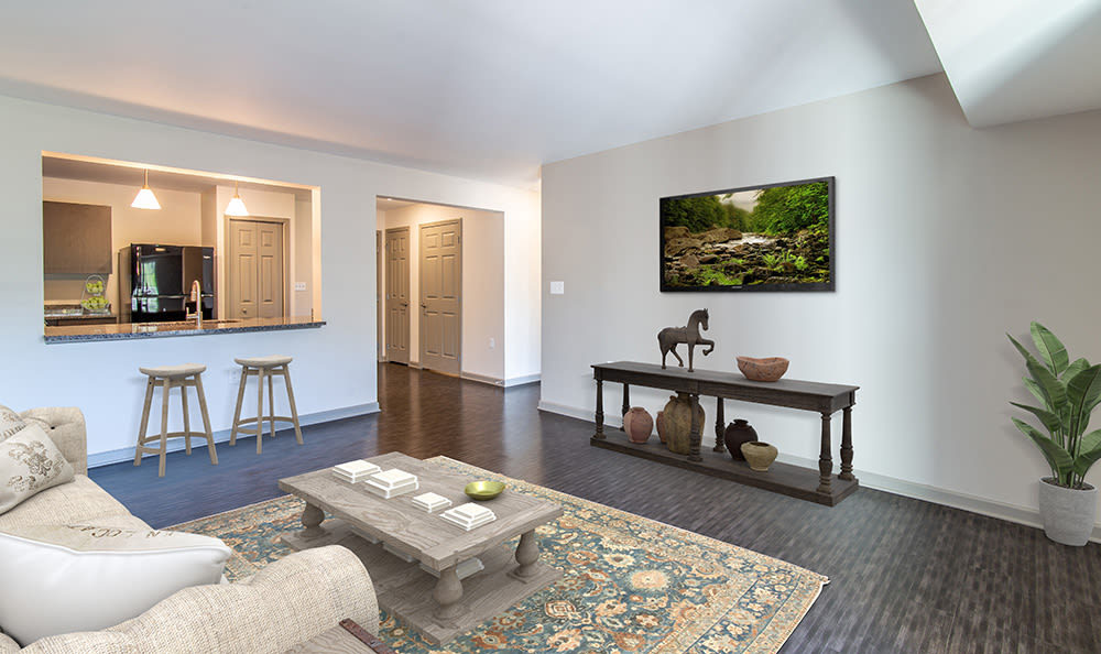 Living room with wood-style flooring at Greenwood Cove Apartments in Rochester, New York