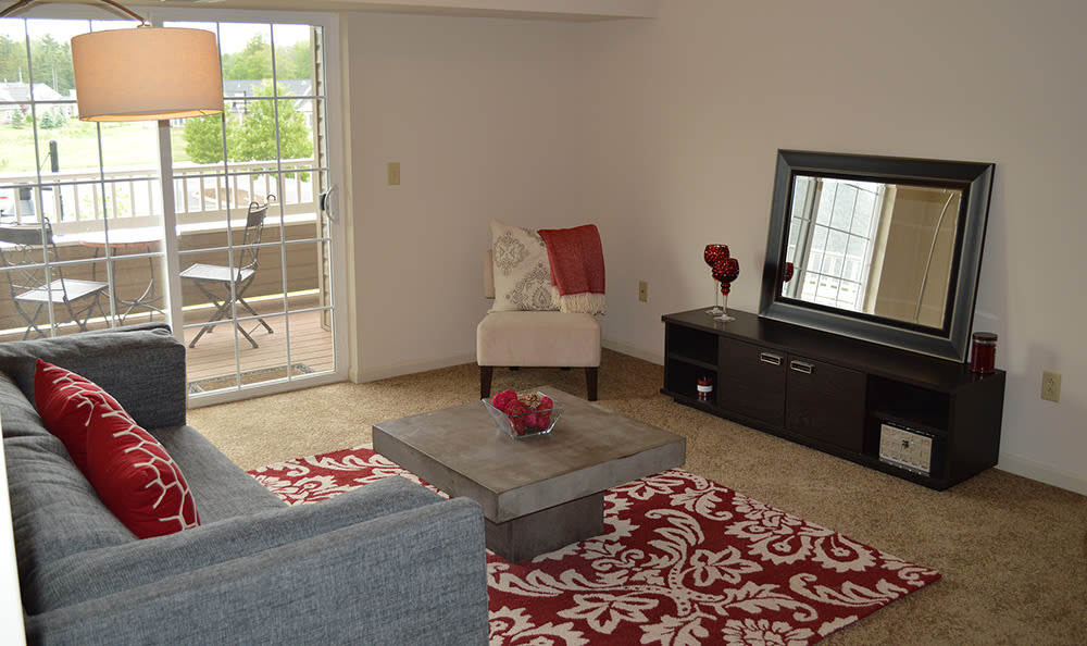 Living room with patio access at Greenwood Cove Apartments in Rochester, New York