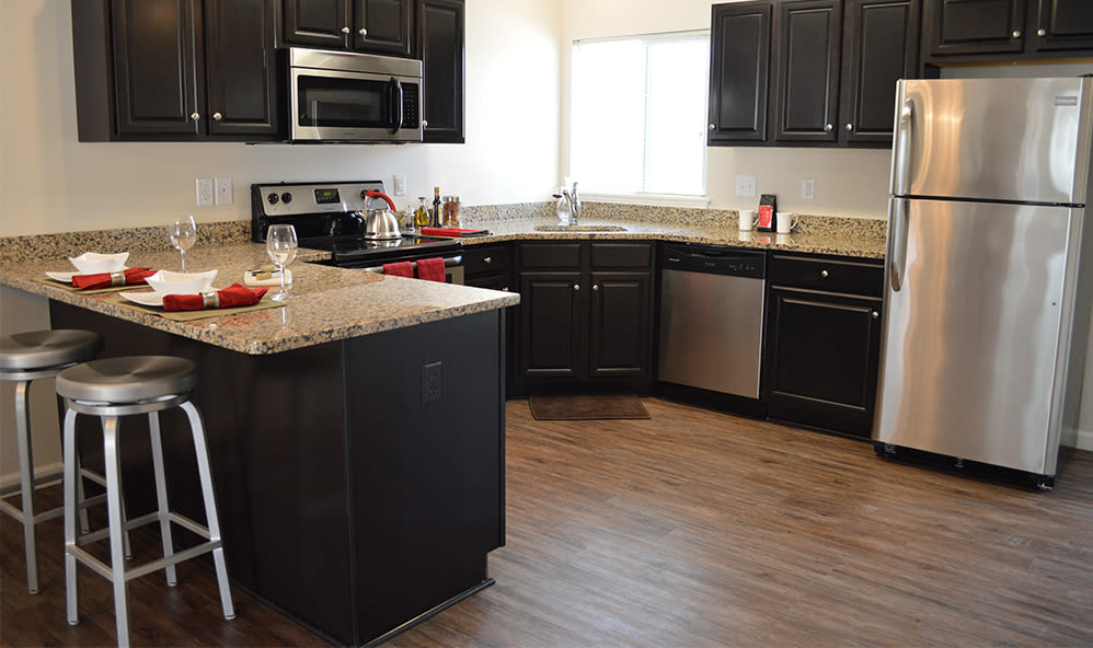 Modern kitchen with granite countertops at Auburn Creek Apartments in Victor, New York