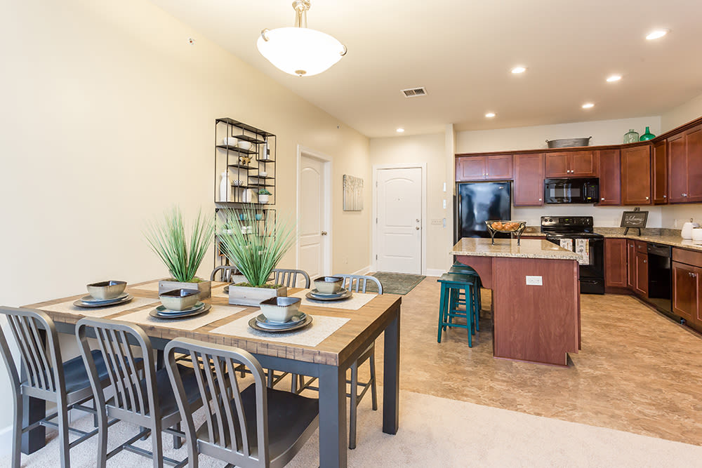 Dining table and kitchen at Gateway Landing on the Canal home in Rochester, New York