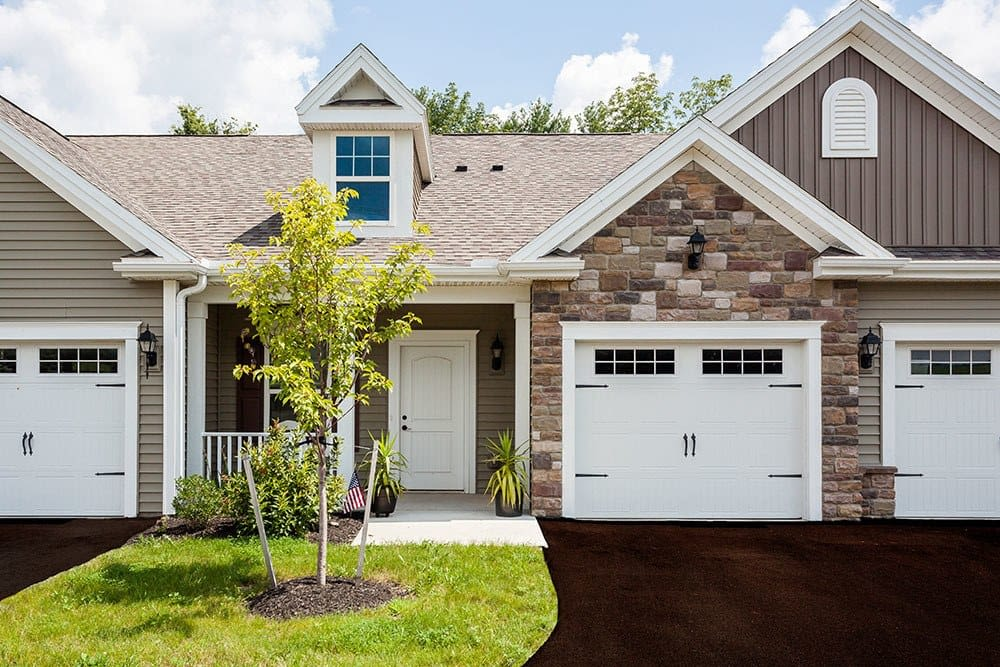 Townhouse with a front lawn at The Links at CenterPointe Townhomes in Canandaigua, New York