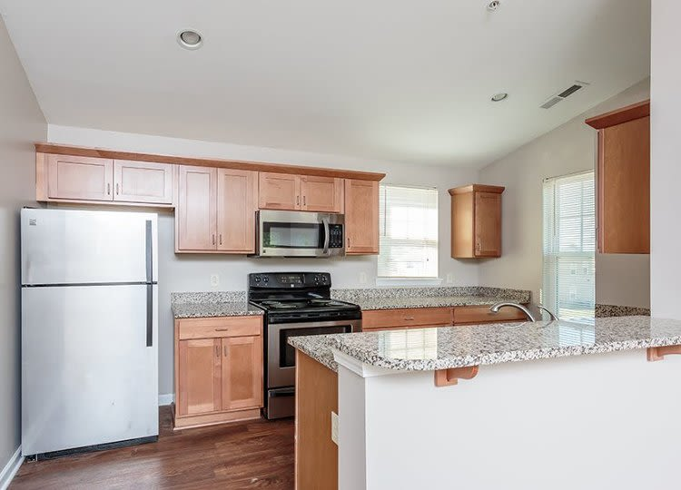 Well-equipped kitchen with granite counters at Webster Green in Webster, New York