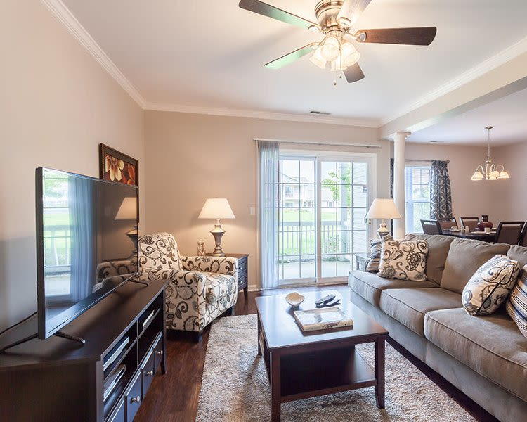 Bright living room with patio access at Oakmonte Apartments in Webster, New York