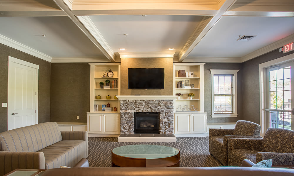 Clubhouse fireplace with some comfy chairs at Preserve at Autumn Ridge in Watertown, New York