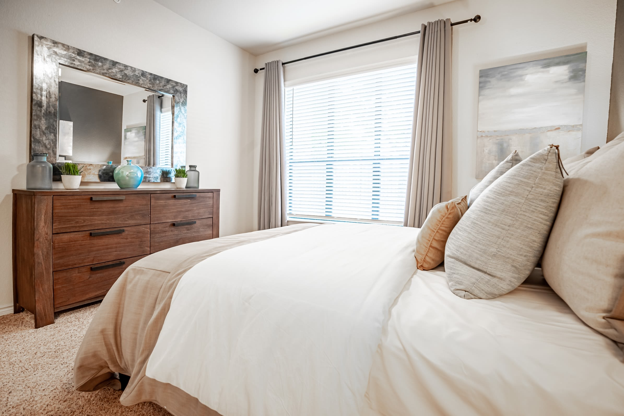 Comfortable bedroom with a large window at The Asten at Ribelin Ranch in Austin, Texas