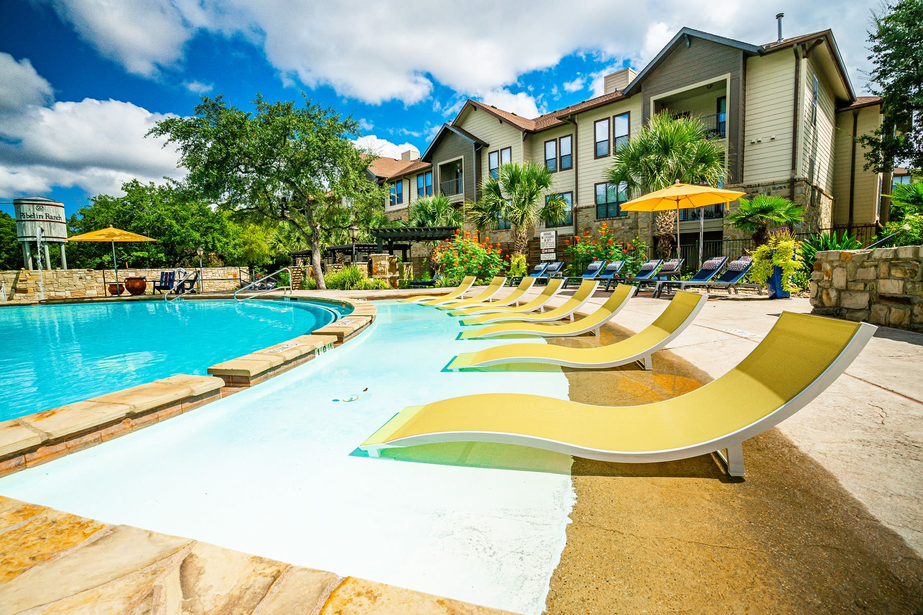 Peaceful poolside deck and lawn chairs at The Asten at Ribelin Ranch in Austin, Texas