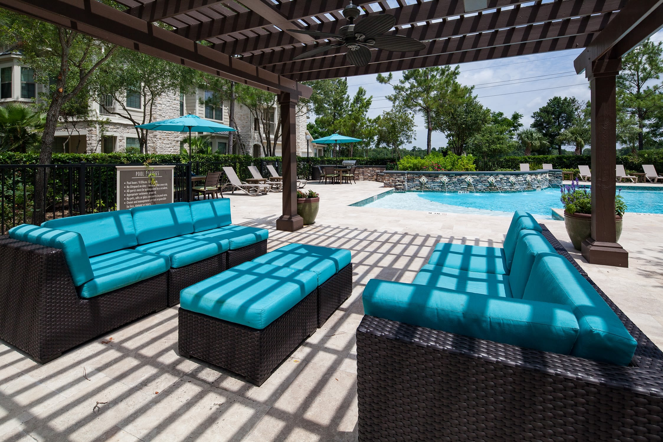 Shaded lounge chairs outside by pool at Lakefront Villas in Houston, Texas