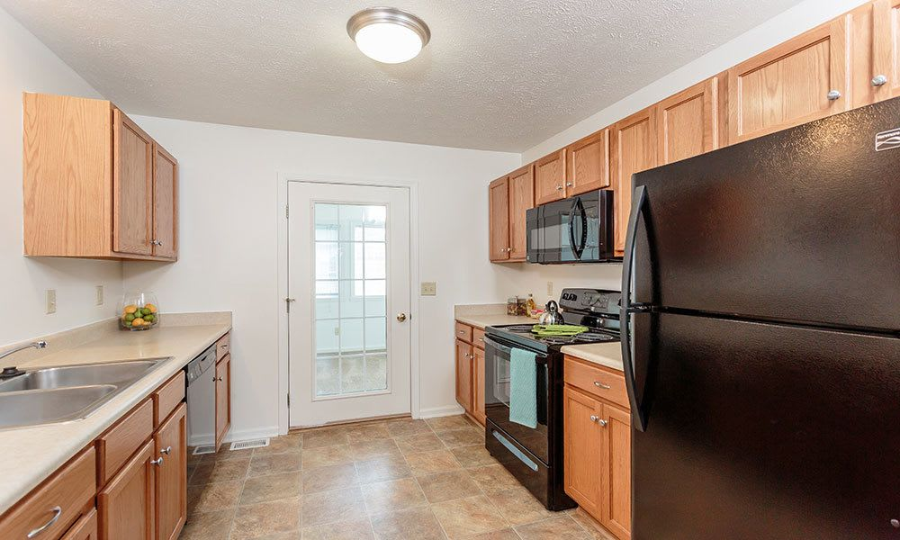 Kitchen with black appliances at Hickory Hollow in Spencerport, New York