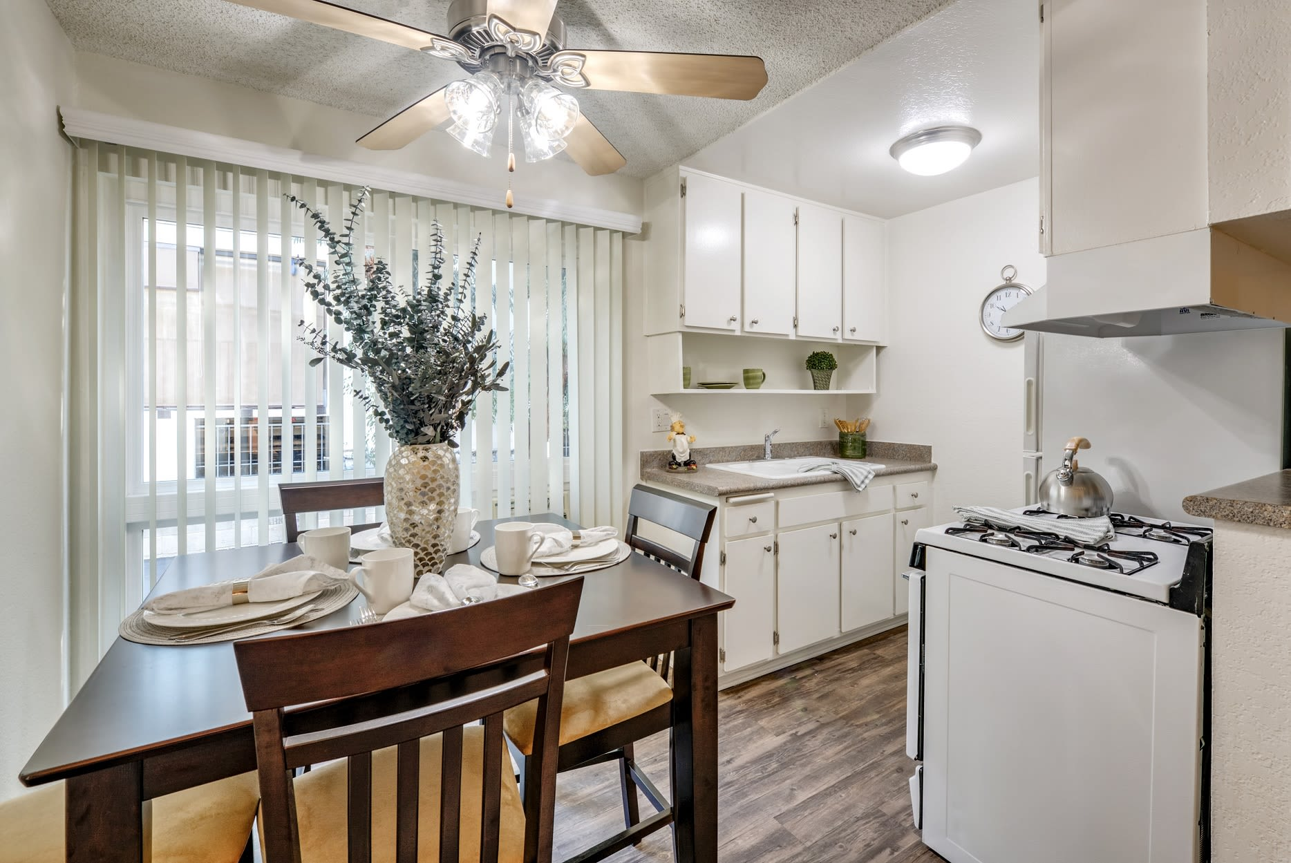 Kitchen and dining area with wood style floors at The Newporter in Tarzana, California