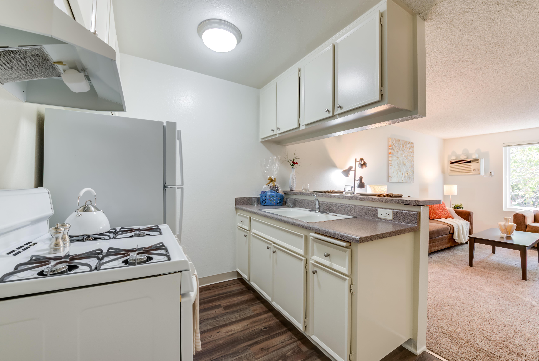 Kitchen with wood style floors and breakfast bar at The Newporter in Tarzana, California