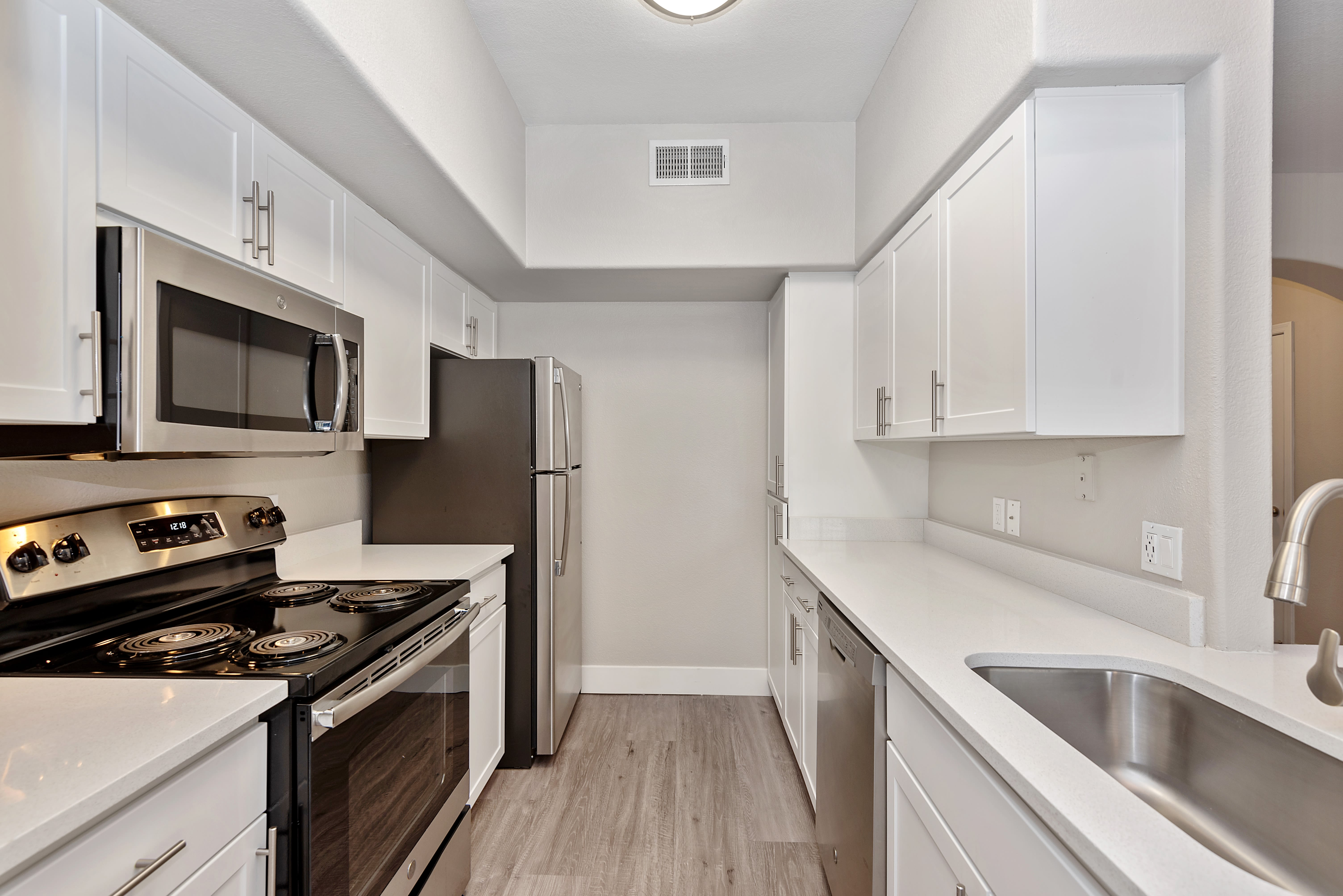 Modern kitchen with hardwood floors at The Retreat Apartments