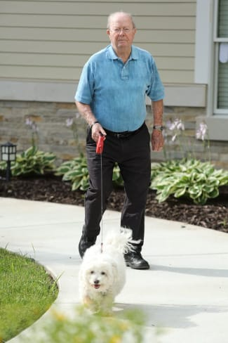 independent living resident walking his dog at The Heritage at Fox Run