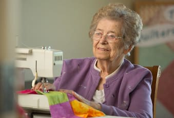 Resident sewing at The Heritage at Fox Run in Council Bluffs