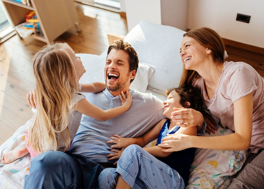 Happy family laughing together at 7100 South Shore Apartment Homes in Chicago, Illinois