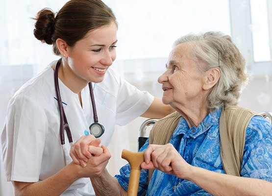 Nurse happily assisting an elderly woman at Grand Villa of Sarasota in Sarasota, Florida