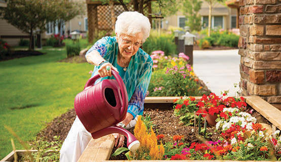 A resident watering flowers at The Heritage at Fountain Point in Norfolk, Nebraska